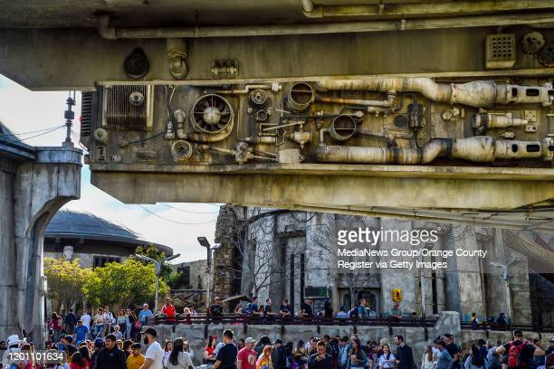 """The front of the Millennium Falcon hangs over crowds at Star Wars: Galaxy""""u2019s Edge inside Disneyland in Anaheim, CA, on Tuesday, Jan 7, 2020."""