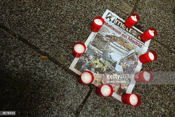 The front page of a spanish newspaper is seen held down by candles on March 12 2004 in central Madrid Spain At least 198 people were killed in the...