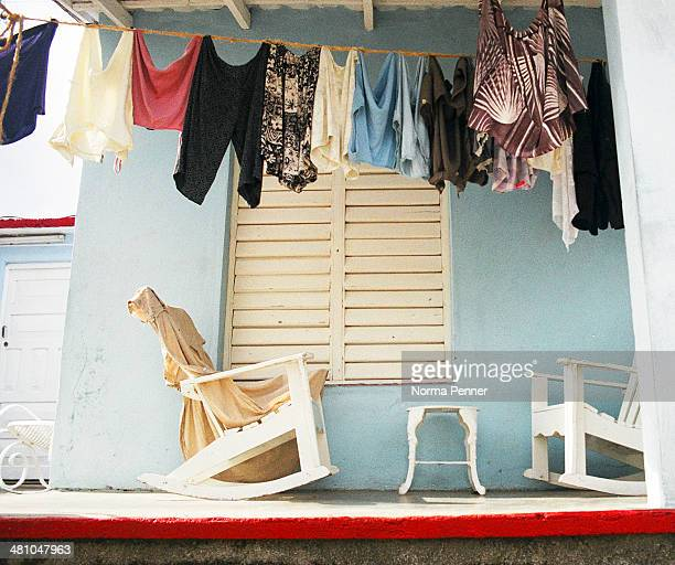 CONTENT] The front porch of a simple home in Vinales Cuba The draping clothesline frames the view of the rocking chairs The turquoise wall is...