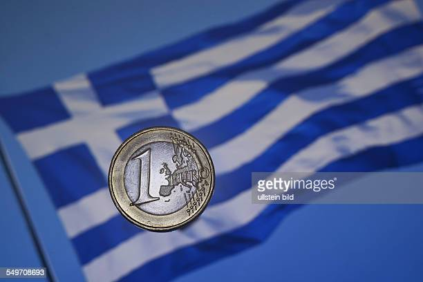 the front side of a Greek Euro coin in front of the Greek national flag