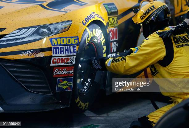 The front tire changer for Erik Jones driver of the DEWALT Toyota works to remove lug nuts during the Monster Energy NASCAR Cup Series Folds of Honor...
