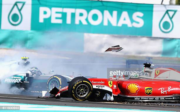The front wing of Sebastian Vettel of Germany driving the Scuderia Ferrari SF16H Ferrari 059/5 turbo flies into the air as Nico Rosberg of Germany...