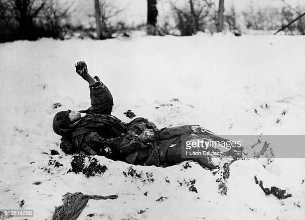 The frozen body of a German Nazi soldier, a victim of American bombing, lies in the snow where he fell in Belgium during World War II.   Location:...