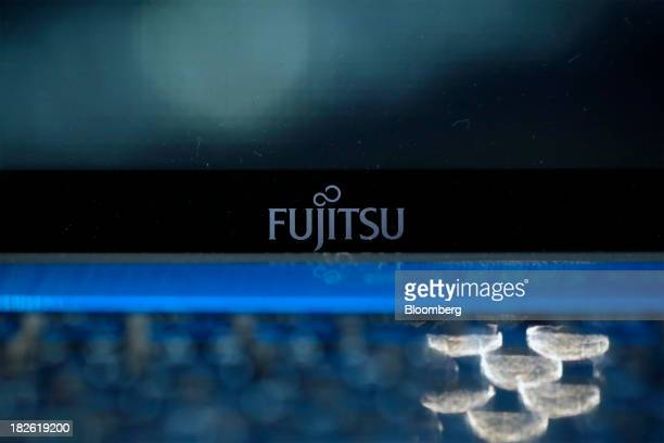 The Fujitsu Ltd logo is displayed on a laptop computer at the company's stand at the CEATEC Japan 2013 exhibition in Chiba City Japan on Tuesday Oct...