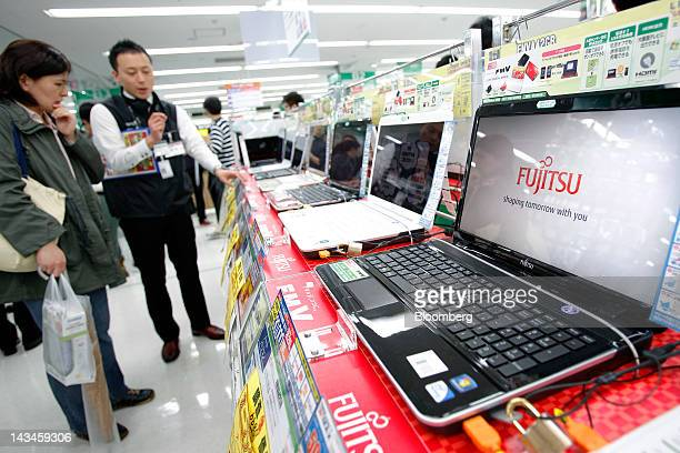 The Fujitsu Ltd logo is displayed on the company's FMV laptop computer as a sales clerk speaks to a customer at the Labi Ofuna electronics store...