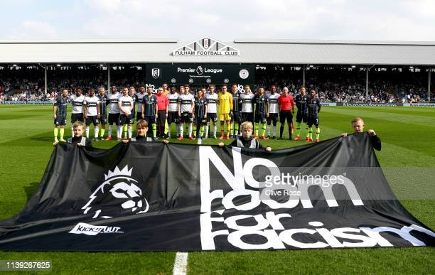 The Fulham and Manchester City players stand with the match officials in protest against racism prior to the Premier League match between Fulham FC...