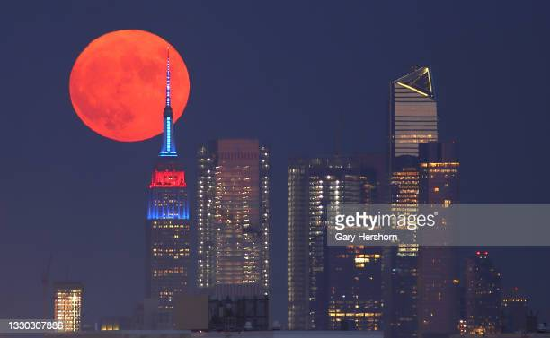 The full Buck Moon or Thunder Moon passes behind Hudson Yards and the Empire State Building lit in the flag colors of countries competing in the...
