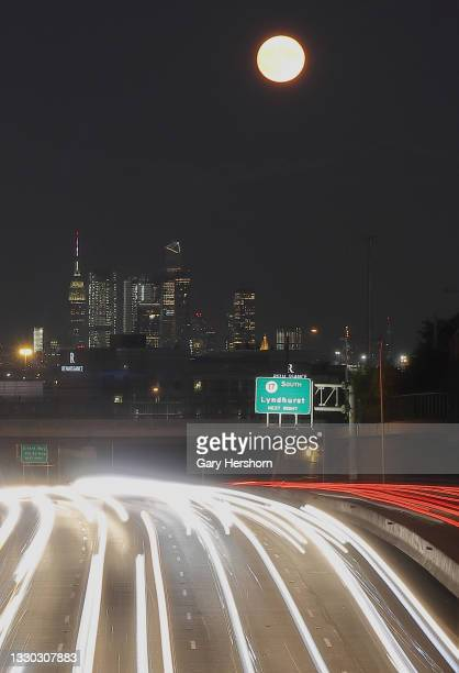 The full Buck Moon or Thunder Moon rises above Hudson Yards and the Empire State Building in New York City and cars driving on Route 3 on July 23,...