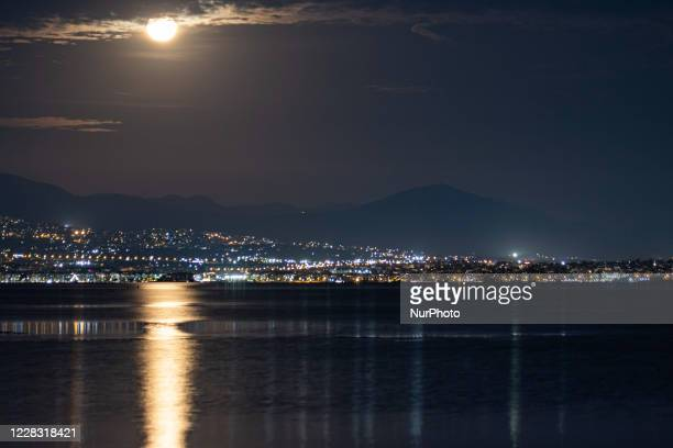 The Full Corn Moon as seen behind Hortiatis mountain over the city of Thessaloniki in Northern Greece, captured from Kalochori Lagoon and National...