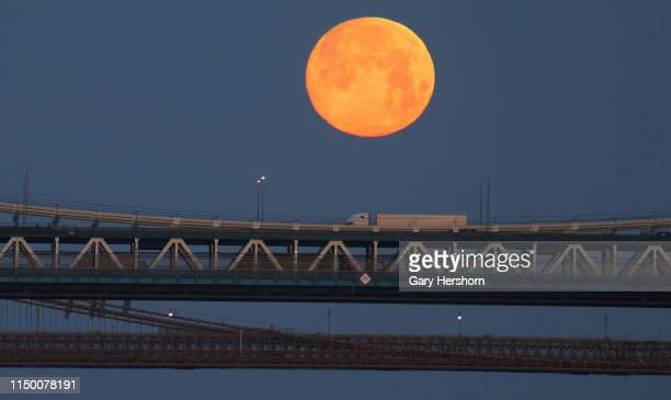 The full Flower Moon sets behind the Manhattan Bridge and Brooklyn Bridge at sunrise on May 18 2019 in New York City