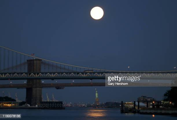 The full Flower Moon sets behind the Statue of Liberty Brooklyn Bridge and Manhattan Bridge at sunrise on May 18 2019 in New York City