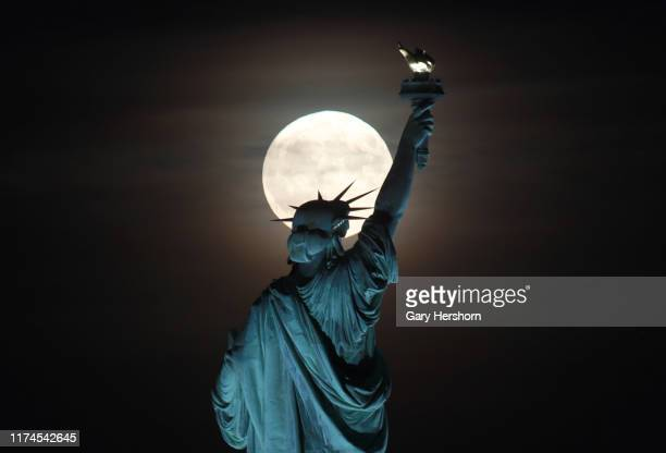 The full Harvest Moon rises behind the Statue of Liberty in New York City on September 13 2019 as seen from Jersey City New Jersey
