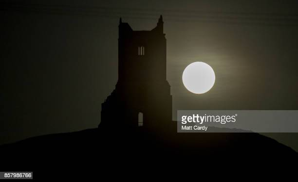 The full Harvest moon rises over the ruins of St Michael's Church a scheduled monument on the top of Burrow Mump on October 5 2017 in Somerset...