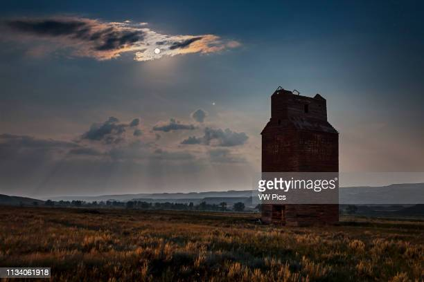 The Full Moon and Mars rising into the southeast over the long abandoned grain elevator at Dorothy Alberta in the Red Deer River valley Alberta This...