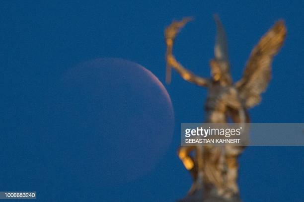 The full moon appears behind a golden angel statue on the roof of the Academy of Fine Arts during a 'blood moon' eclipse over Dresden eastern Germany...