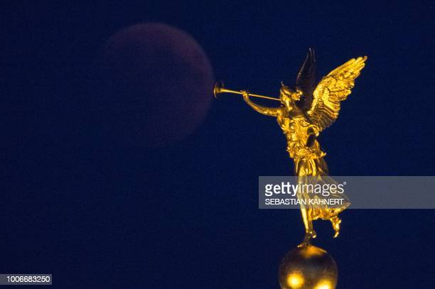 The full moon appears behind a golden trumpet angel statue during a 'blood moon' eclipse over Dresden eastern Germany on July 27 2018 The longest...