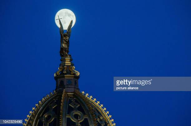 The full moon behind the golden dome and figure of the Archangel Michael atop Schwerin Palace Germany 2 July 2015 PHOTO JENS BUETTNER/DPA | usage...