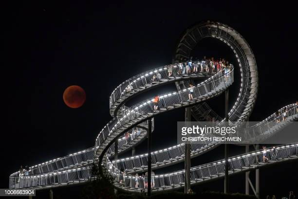 The full moon can be seen behind the landmark 'Tiger and Turtle' sculpture and walkway during a 'blood moon' eclipse over Duisburg western Germany on...