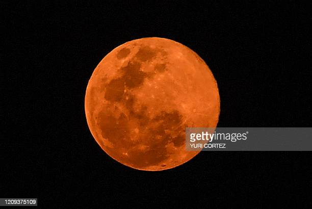 The full moon is photographed during the phenomenon known as the pink supermoon over the sky in San Salvador on April 7 2020 A supermoon occurs when...