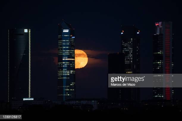 The full moon of May also known as Flower Moon rises between the Four Towers Business area skyscrapers. A rare simultaneous occurrence of a blood...