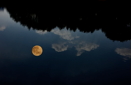 The full moon reflected on the lake surface 1134803961