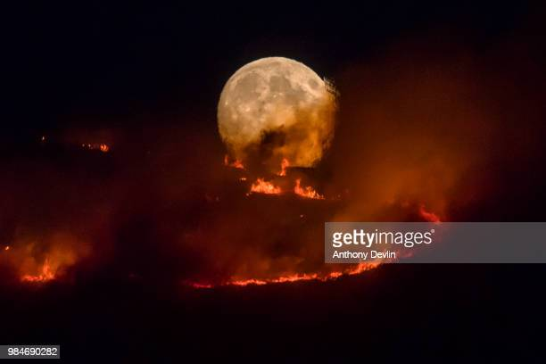 The full moon rises behind burning moorland as a large wildfire sweeps across the moors between Dovestones and Buckton Vale in Stalybridge Greater...