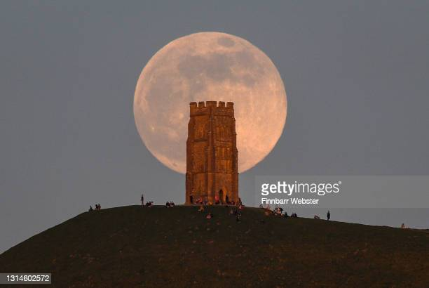 The full moon rises behind Glastonbury Tor on April 26, 2021 in Glastonbury, England. The pink supermoon will reach peak size in the early hours of...