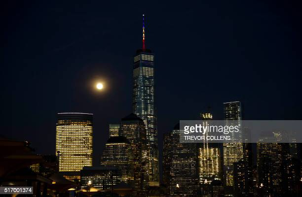 The full moon rises behind One World Trade Center on March 22, 2016 in New York, it's mast displaying the colors of the Belgian flag in a show of...