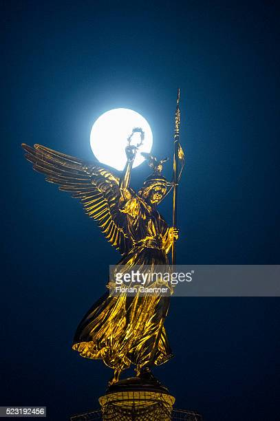 The full moon rises behind the Berlin Victory Column on April 21 2016 in Berlin Germany
