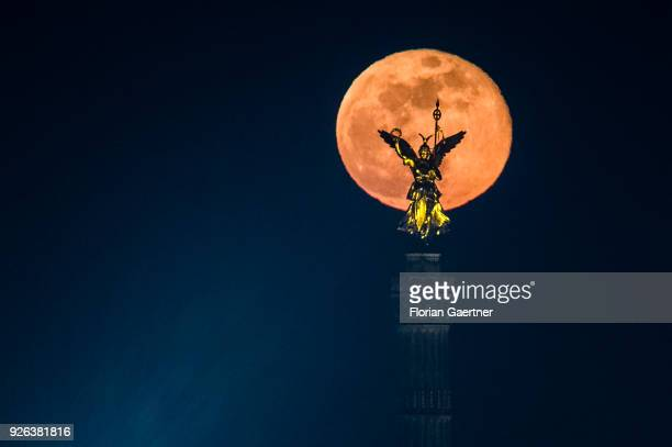 The full moon rises behind the so called 'Goldelse' on the top of the Berlin Victory Column on March 02 2018 in Berlin Germany