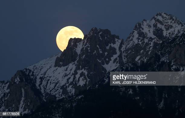 The full moon rises in Buching southern Germany behind the snowcapped Alps on May 10 2017 / AFP PHOTO / dpa / KarlJosef Hildenbrand / Germany OUT