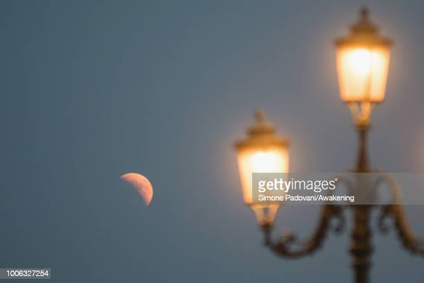 The full moon rises in the Venetian lagoon near San Giorgio Maggiore island just before the total lunar eclipse on July 27 2018 in Venice Italy The...