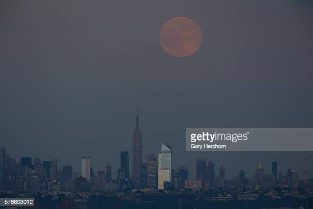 The full moon rises over the Empire State Building and the skyline of New York City on July 19, 2016 as seen from Montclair, NJ.