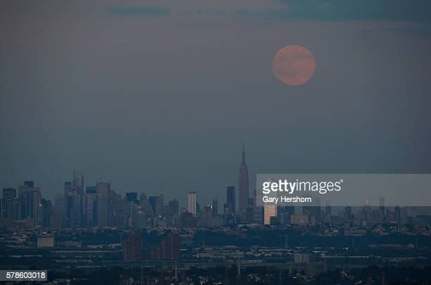The full moon rises over the Empire State Building and the skyline of New York City on July 19 2016 as seen from Montclair NJ