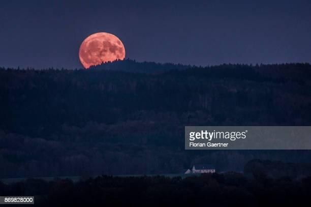 The full moon rises over the mountain 'Koenigshainer Berge' near the germanpolish border in Saxony on November 03 2017 in Koenigshain Germany