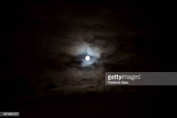 The full moon seen in the sky surrounded by clouds