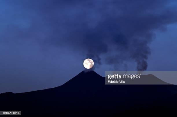 The full moon sets behind the southeast crater of Mount Etna, steaming in apparent stillness on February 28, 2021 in Catania, Italy. The shots were...