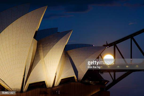 The full moon sets behind the Sydney Opera House and Harbour Bridge just before dawn