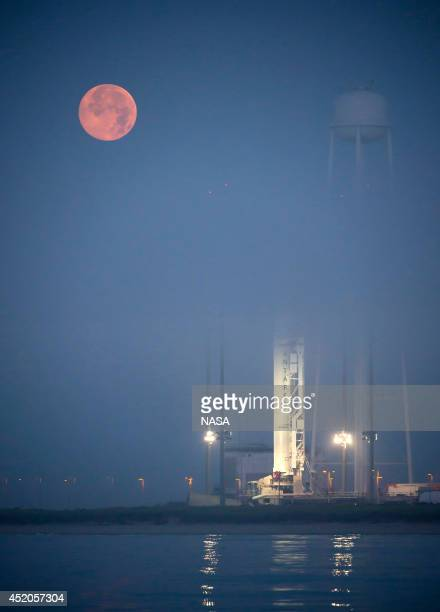 The full Moon sets in the fog behind the Orbital Sciences Corporation Antares rocket with the Cygnus spacecraft onboard on July 12 at NASA's Wallops...