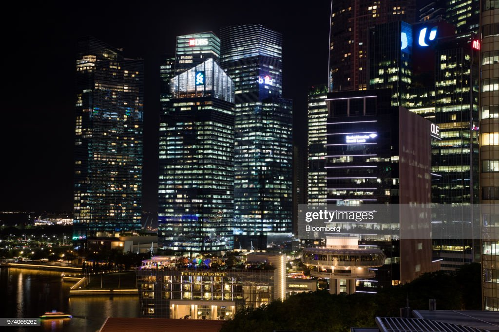 The Fullerton Hotel, center left, and commercial buildings in the central business district are illuminated at night in Singapore, on Wednesday, June 13, 2018. Tourism as well as the consumer sector will likely see a lift thanks to the influx of international media at the recent DPRK-USA Summit, according to RHB Research Institute Singapore Pte. Photographer: SeongJoon Cho/Bloomberg via Getty Images