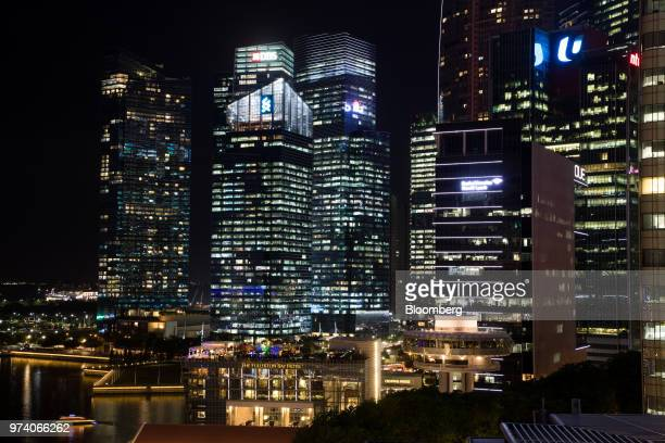 The Fullerton Hotel center left and commercial buildings in the central business district are illuminated at night in Singapore on Wednesday June 13...