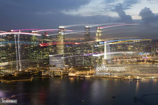 The Fullerton Hotel center right and commercial buildings standing in the central business district left are illuminated at dusk in Singapore on...