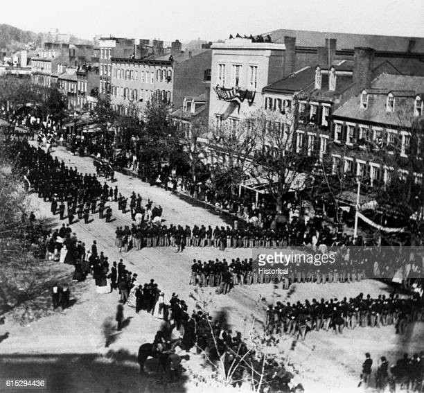 The funeral procession for President Abraham Lincoln passes down a city street in April of 1865