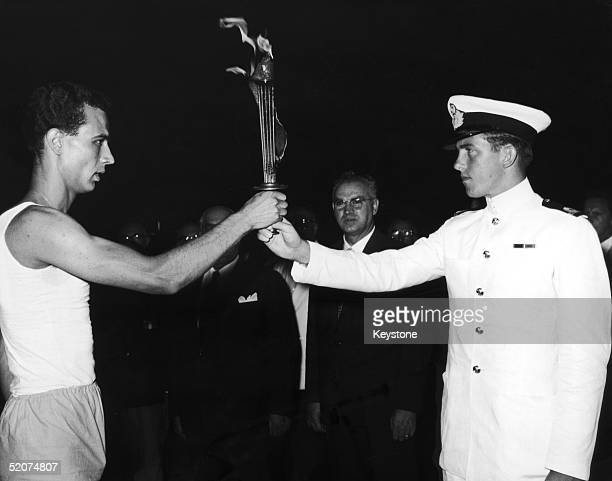 The future King Constantine of Greece hands over the Olympic flame which will be transported from Greece to Italy on board the Amerigo Vespucci for...