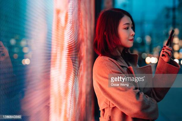 the future of digital world - young woman with smartphone standing against a digital display. - mobile phone stock pictures, royalty-free photos & images