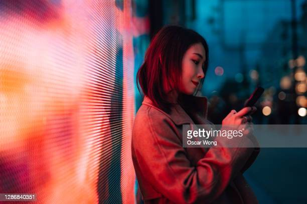 the future of digital world - young woman with smartphone standing against a digital display. - illuminated stock pictures, royalty-free photos & images