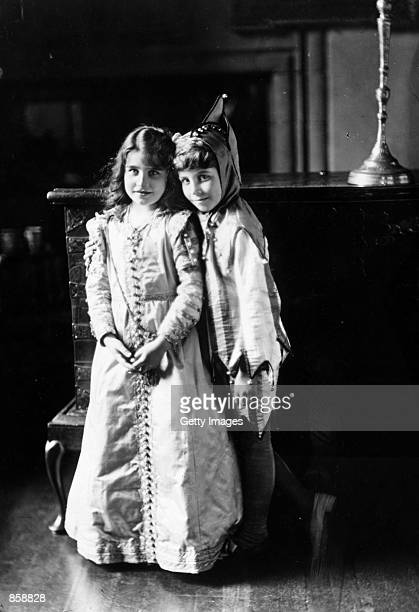 The future Queen Elizabeth Lady Elizabeth BowesLyon left wears a fancydress costume circa 1909 with her brother Lord David BowesLyon at Glamis Castle...