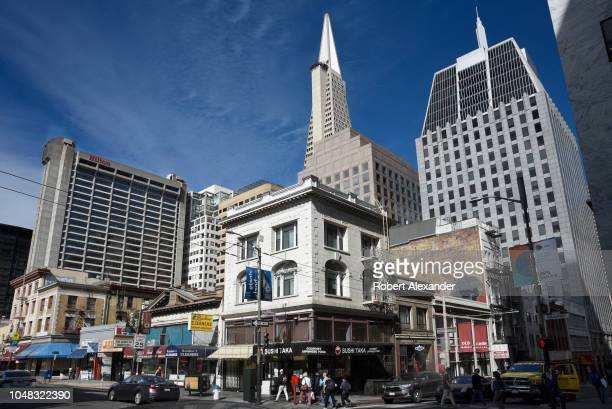 The futuristic Transamerican Pyramid building soars above other skyscrapers and modern buildings, older buildings and busy streets in San Francisco,...