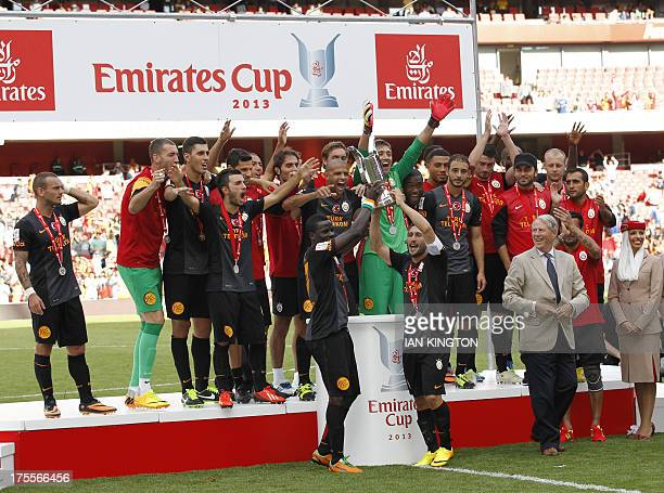 The Galatasaray squad celebrate with the trophy beating Arsenal in the preseason friendly football match at The Emirates Stadium in north London on...