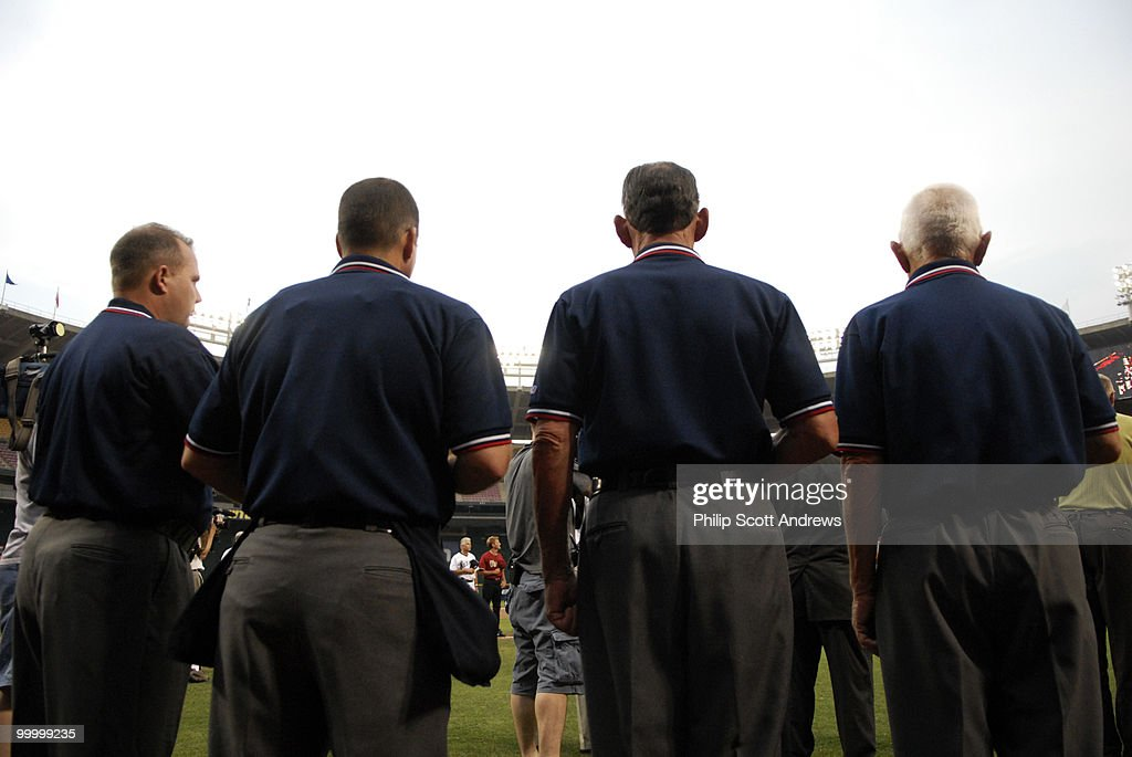 The games umpires pause during the singing of the national anthem.